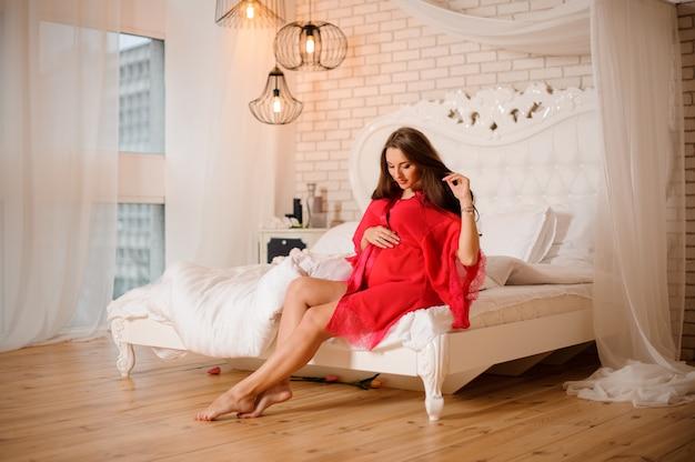 Donna incinta attraente in veste da camera rosa che si siede sul letto