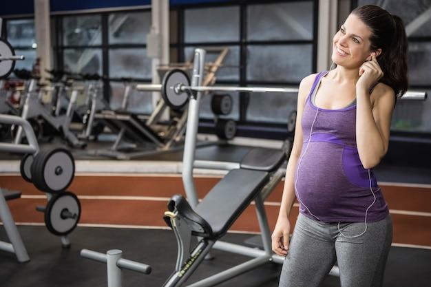Donna incinta che ascolta la musica in palestra