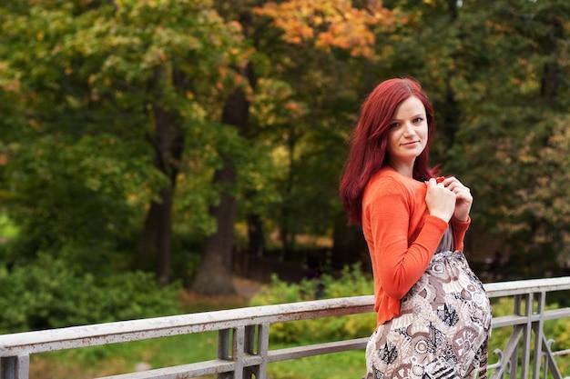 Donna incinta che cammina nel parco di autunno