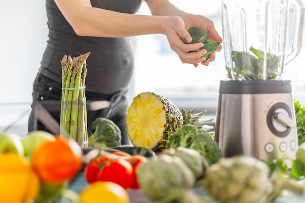Donna incinta che cucina frullato sano