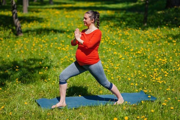 Donna incinta che fa asana all'aperto