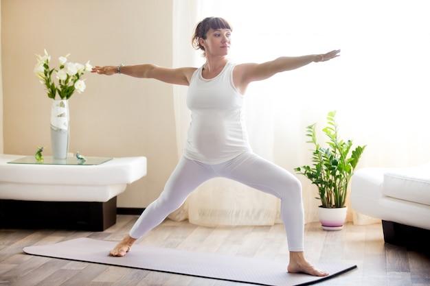 Donna incinta che fa guerriero due posa di yoga a casa