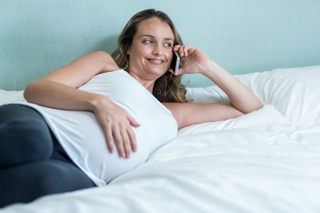 Donna incinta che fa una telefonata sul suo letto