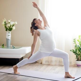 Donna incinta che fa viparita virabhadrasana yoga posa a casa