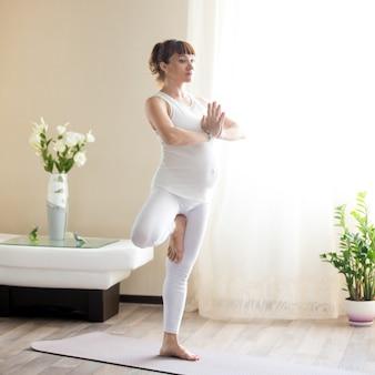 Donna incinta che fa vrksasana yoga posa a casa