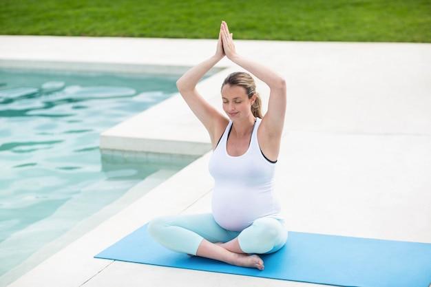 Donna incinta che fa yoga accanto alla piscina