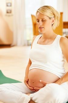 Donna incinta che fa yoga di gravidanza