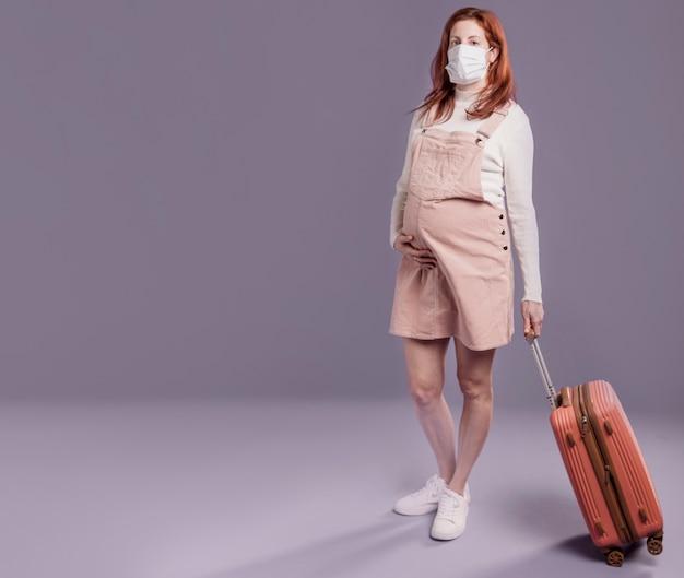 Donna incinta che indossa una maschera protettiva