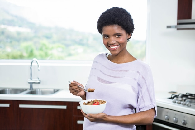 Donna incinta che mangia cereale in cucina