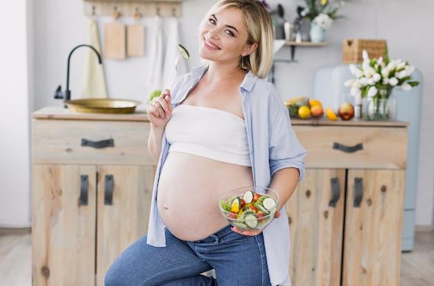 Donna incinta che mangia insalata mentre esaminando la macchina fotografica