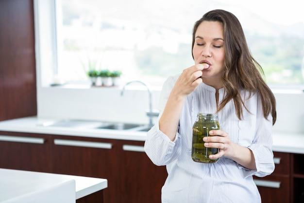 Donna incinta che mangia sottaceti in cucina