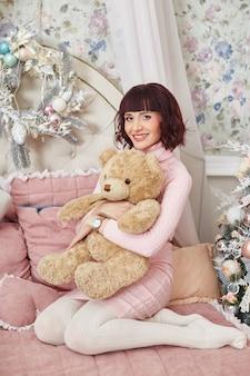 Donna incinta che posa sul letto con un orsacchiotto