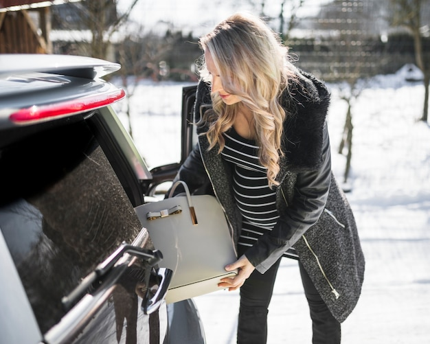Donna incinta che prende borsa dall'auto