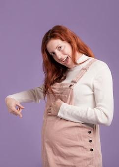 Donna incinta che punta alla sua pancia incinta