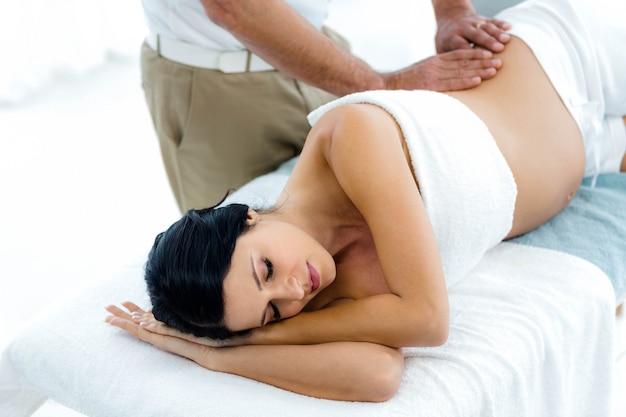 Donna incinta che riceve un massaggio alla schiena dal massaggiatore a casa