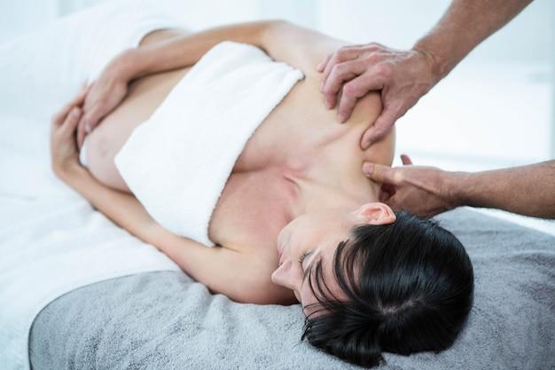 Donna incinta che riceve un massaggio alla schiena dal massaggiatore presso il centro benessere