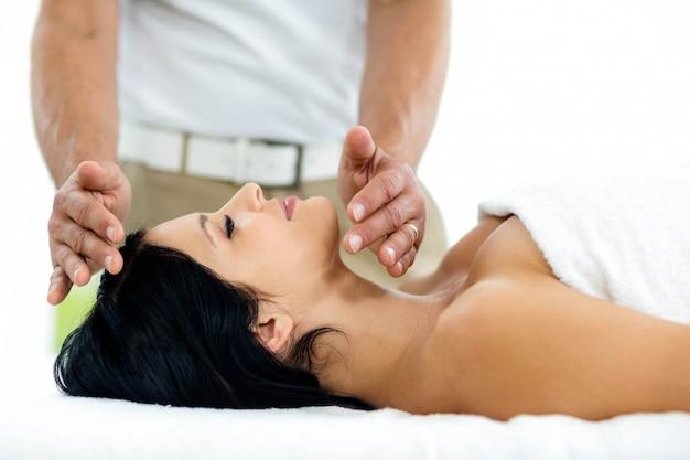 Donna incinta che riceve un trattamento termale dal massaggiatore a casa
