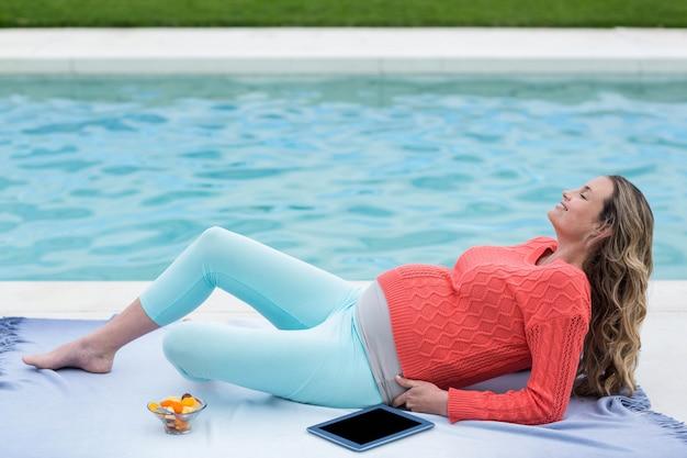 Donna incinta che si distende all'esterno e utilizza la tavoletta accanto alla piscina