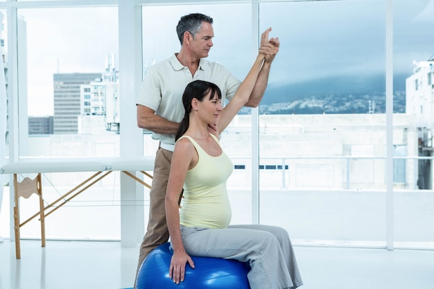 Donna incinta che si esercita con il fisioterapista sulla palla di esercizio a casa
