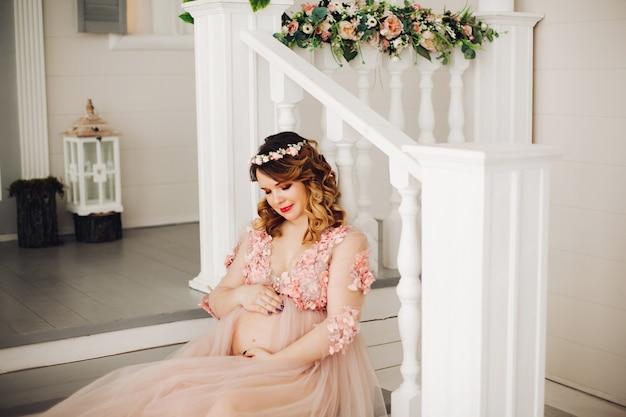 Donna incinta che si siede con il diadema della corona