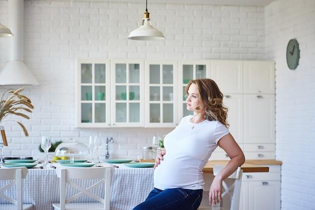 Donna incinta che si siede in cucina. copia spazio.
