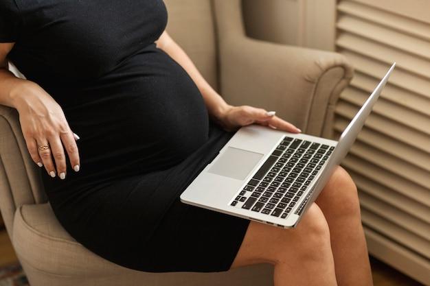 Donna incinta che si siede su una sedia e che lavora al computer portatile
