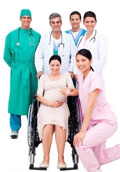 Donna incinta che si siede sulla sedia a rotelle