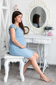 Donna incinta che si siede sulla sedia d'annata