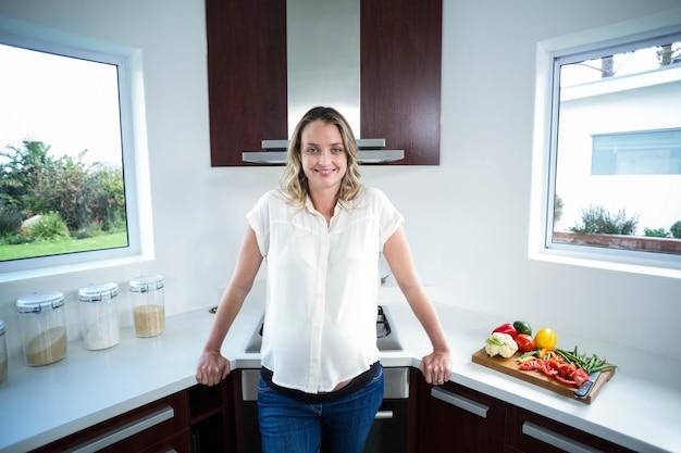 Donna incinta che sorride alla macchina fotografica in cucina
