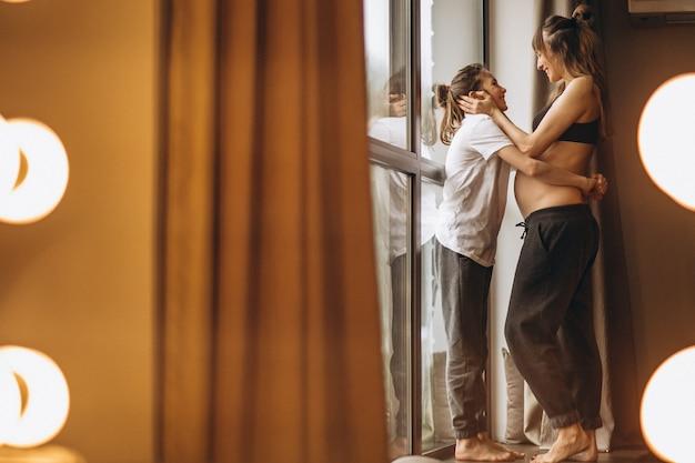 Donna incinta che sta con la figlia dalla finestra