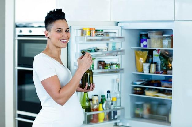 Donna incinta che sta vicino al frigorifero aperto e che mangia i sottaceti