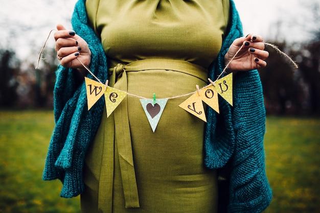 Donna incinta che tiene il segno