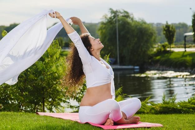 Donna incinta che tiene tessuto bianco su vento