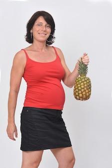 Donna incinta che tiene un ananas su priorità bassa bianca
