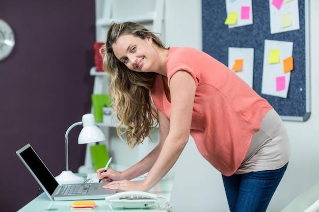 Donna incinta che utilizza computer portatile in un ufficio