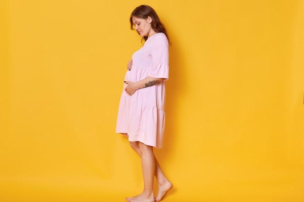 Donna incinta con i capelli annegati, vestito di polvere rosa, che abbraccia la pancia. la femmina elegante e alla moda posa a piedi nudi, guarda il suo addome. concetto di pragnanza e maternità