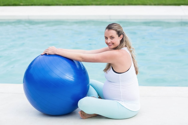 Donna incinta con palla di esercizio di fronte alla piscina