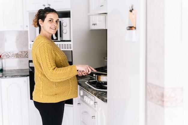 Donna incinta con un maglione giallo che cucina in piedi in una cucina accanto a un frigorifero sorridente