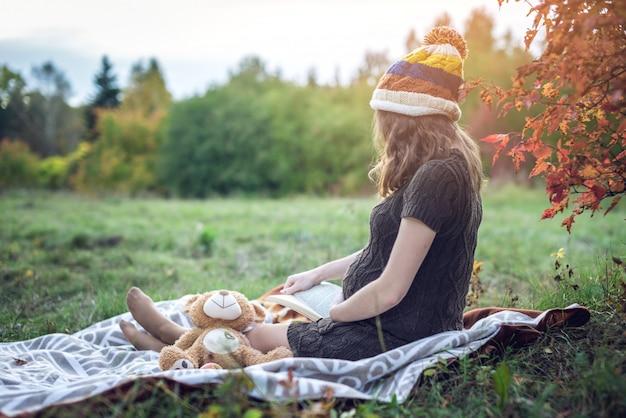Donna incinta con una pancia che legge le storie al bambino