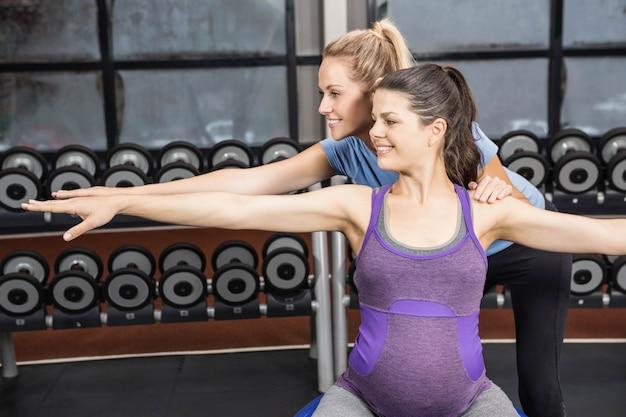 Donna incinta d'aiuto dell'istruttore che si esercita su una palla di esercizio alla palestra