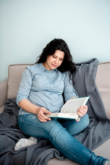 Donna incinta del colpo medio che legge un libro