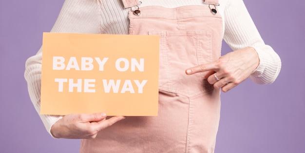Donna incinta del primo piano che indica alla carta con il bambino sul messaggio di modo