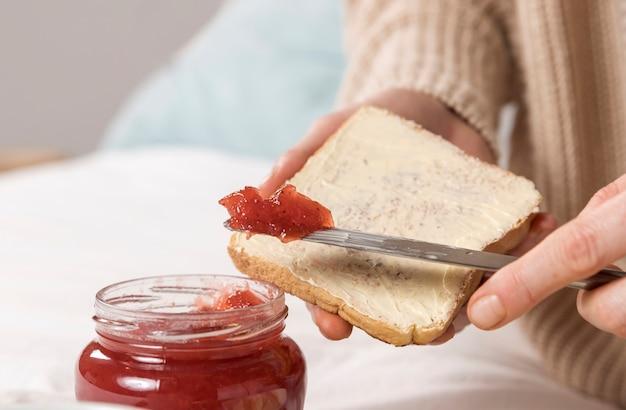 Donna incinta del primo piano che mangia brunch a casa a letto