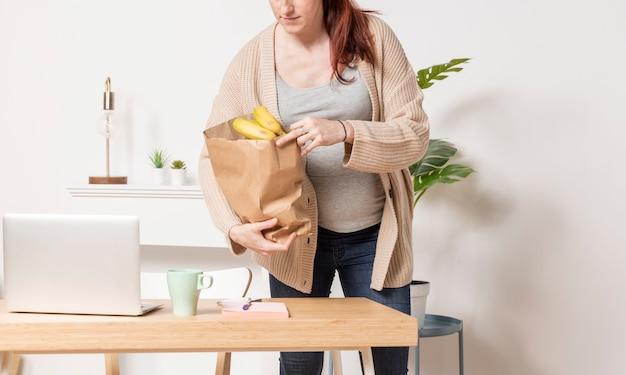 Donna incinta del primo piano con il sacchetto di drogheria