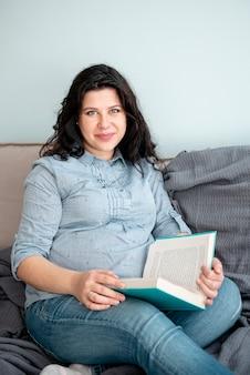 Donna incinta del tiro medio che pone sullo strato con il libro