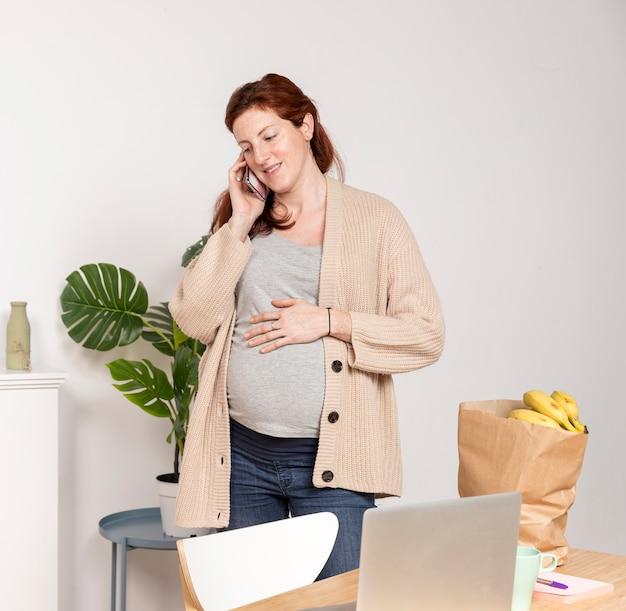 Donna incinta dell'angolo alto che parla sopra il telefono