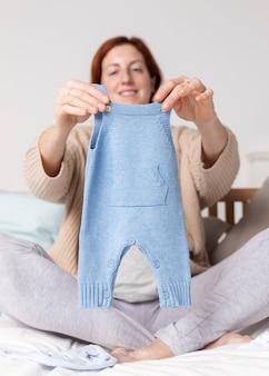Donna incinta di angolo basso che esamina i vestiti del bambino