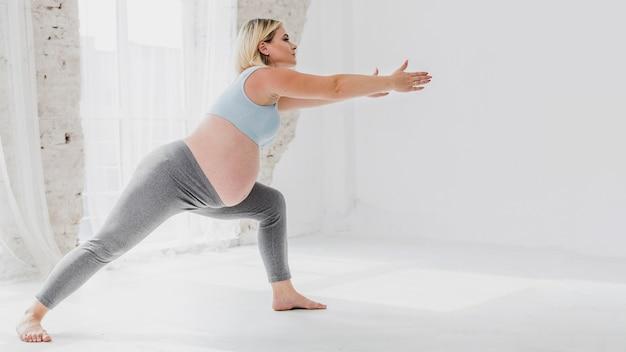 Donna incinta di vista laterale che fa le esercitazioni