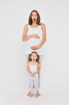 Donna incinta e bambina in abiti sportivi su fondo bianco. le ragazze tengono il suo stomaco.