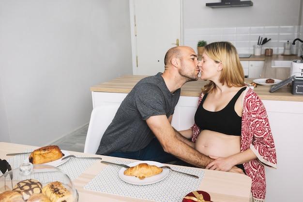 Donna incinta e marito in cucina